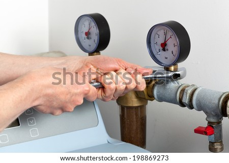 Man hands repairing pressure gauge and valve - stock photo
