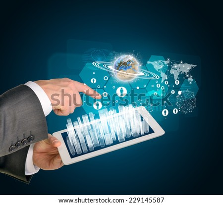Man hands using tablet pc. Business city on touch screen. Earth with business elements near computer. Elements of tgis image furnished by NASA - stock photo