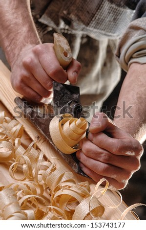 Man hands with carpenters plane on wooden background - stock photo