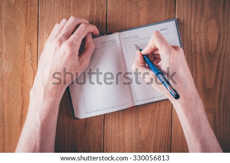 Man hands writing notes in daily planner - stock photo