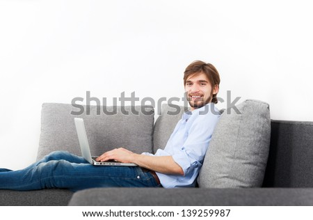 man happy smile with laptop lying on sofa at home, young guy surfing on computer, with copy space on white wall - stock photo
