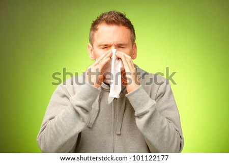 Man having a cold holding tissue and blowing his nose - stock photo