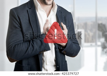 Man having a pain in the heart area, with a warning sign over him - stock photo