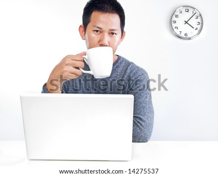 Man having a tea break at his desk - stock photo