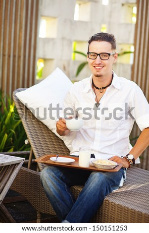 man having breakfast on back yard of his house - stock photo
