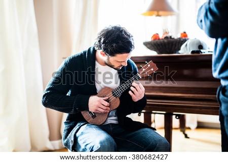 Man having fun while playing on his ukulele - stock photo