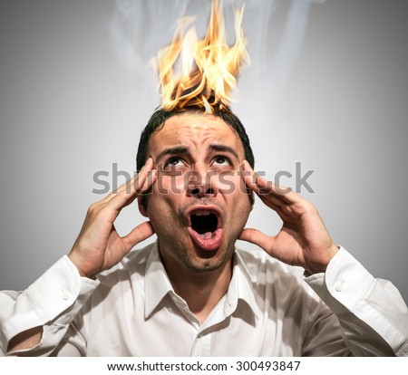 Man having his braing burning up due to stress - stock photo