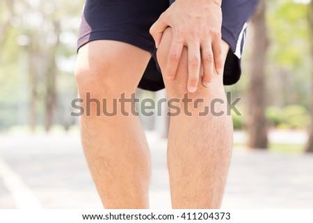 Man having knee pain while exercising - stock photo
