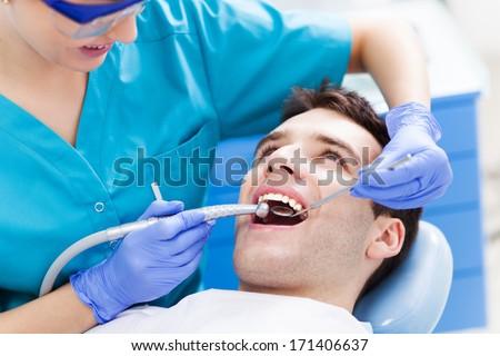 Man having teeth examined at dentists  - stock photo
