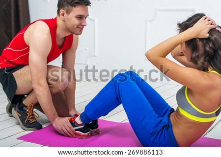 Man helping a woman or girl in making abdominal crunch,  exercises concept training exercising workout fitness aerobic. - stock photo