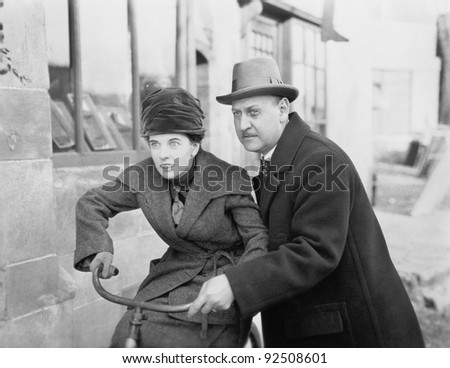 Man helping a woman ride a bicycle - stock photo