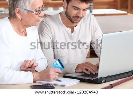 Man helping elderly family member shop on-line - stock photo