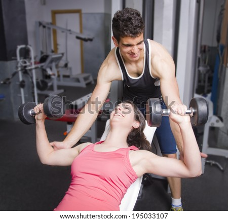 Man helping girl shoulders exercises at old gym - stock photo