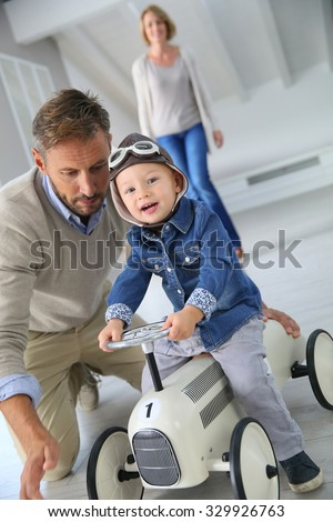 Man helping little boy on a riding toy - stock photo