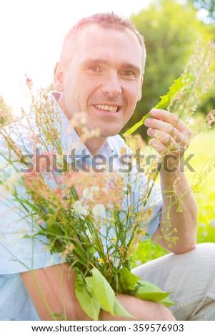 Man herbalist picking up wild herbs  - stock photo