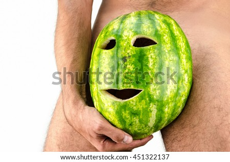 man hides a genitalia with a mask or fruit - stock photo
