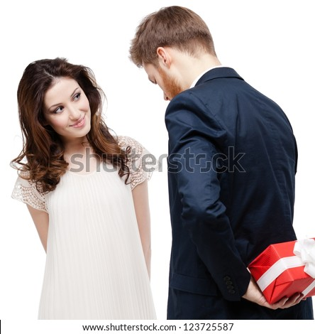Man hides the present behind the back from his pretty girlfriend, isolated on white - stock photo