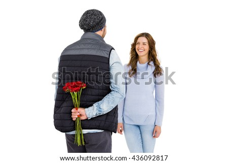 Man hiding a rose behind his back from his woman on white background - stock photo