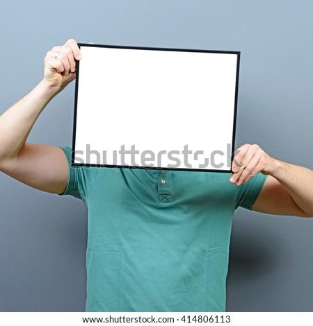 Man hiding behind blank sign board - stock photo