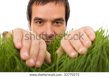 Man hiding behind grass blades - isolated - stock photo