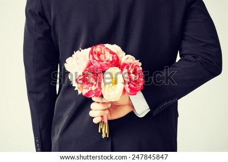 man hiding bouquet of flowers behind his back. - stock photo