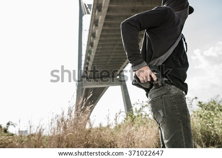 Man hiding his gun in his jeans - stock photo