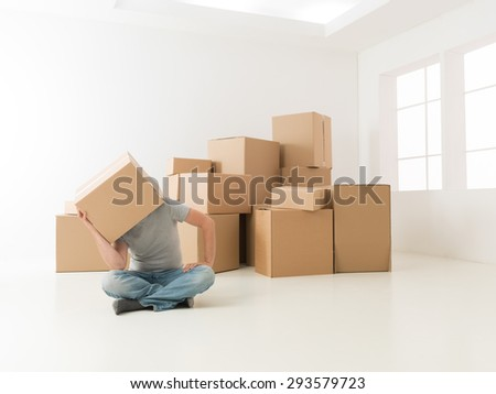 man hiding his head in cardboard box, sitting on floor in new apartment, looking worried or tired - stock photo
