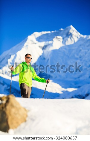 Man hiker or climber accomplish in winter mountains, inspiration and motivation achievement business concept. Success climbing, beautiful inspirational landscape Annapurna mountain in background. - stock photo