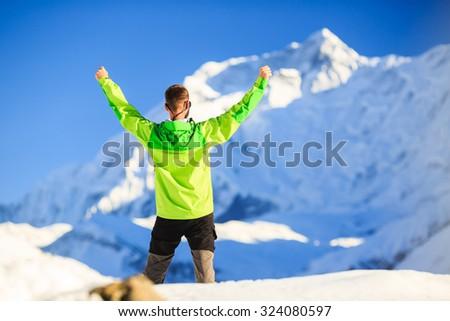 Man hiker or climber achievement in winter mountains, inspiration and motivation achievement business concept. Success accomplish climbing, beautiful inspirational landscape with Annapurna mountain. - stock photo