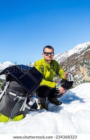 Man hiker trekking and camping in base camp, high Himalaya Mountains in Nepal. Backpacker using equipment, resting and drinking tea in white winter or autumn nature on snow. Annapurna circuit trek. - stock photo