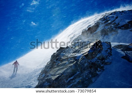 man hiking mountain during snow storm with blue sky - stock photo