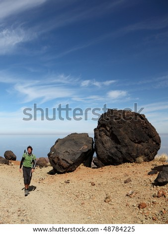 Man Hiking on Teide Tenerife. Man hiking / backpacking within the national park of Teide on Tenerife. A view of the hiking path showing many of the big black Teide Eggs. Blue sky for copy space. - stock photo
