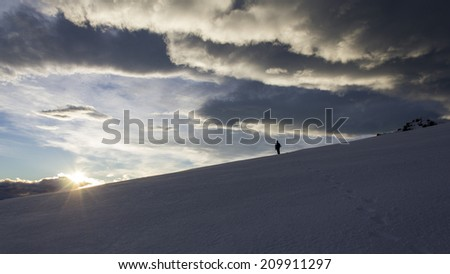 Man Hiking Over Snowy Hill Towards Sunset in New Zealand. - stock photo