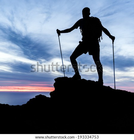 Man hiking silhouette accomplish in mountains, sunset and ocean. Male hiker with walking sticks on top of mountain looking at beautiful night landscape. - stock photo