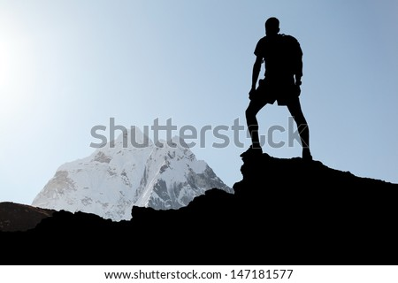 Man hiking silhouette in Himalaya mountains. Male hiker with backpack on top of mountain looking at beautiful morning at Mount Ama Dablam in Himalayas, Nepal - stock photo