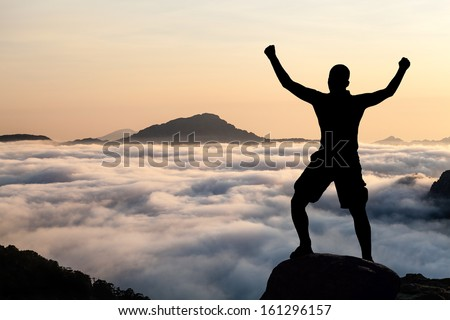 Man hiking silhouette in mountains, sunset and clouds. Male climber hiker arms outstretched on top of mountain after success climbing looking at beautiful sunset sky night landscape. - stock photo
