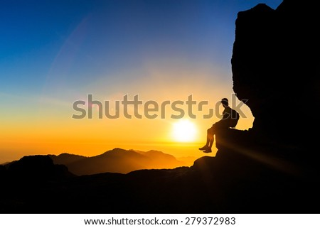 Man hiking silhouette in mountains, sunset and ocean. Male hiker with backpack on top of mountain looking at beautiful night landscape view and blue sky, freedom concept - stock photo