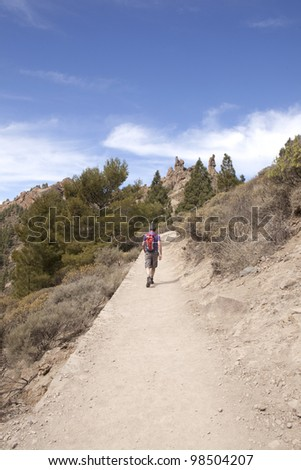 Man hiking  with backpack on footpath in mountains - stock photo