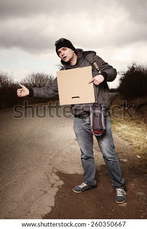Man hitch-hiking on local European route with blank cardboard - stock photo