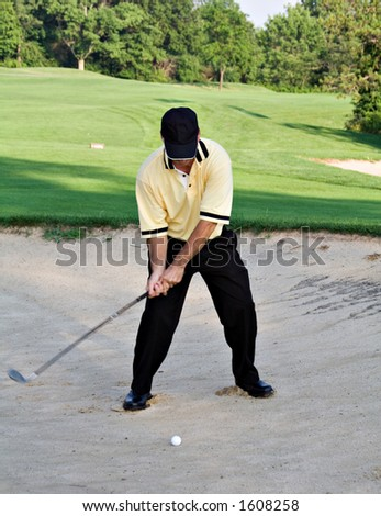 Man hitting ball out of sand trap - golfing. - stock photo