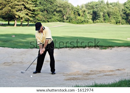 Man hitting from sandtrap - dressed impeccably for the game. - stock photo