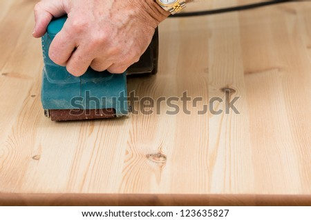 Man holding a belt sander on pine floor or table sanding surface - stock photo