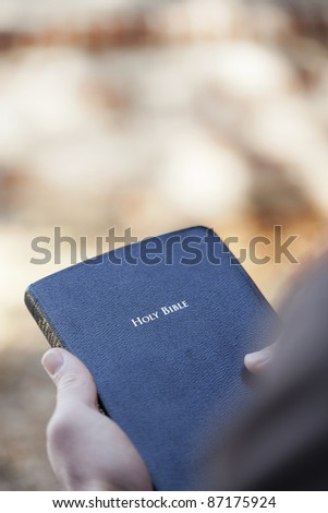 Man holding a Bible outside with shallow depth of field. - stock photo