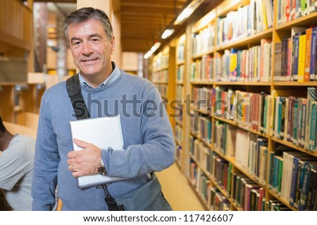 Man holding a book to his chest in a library - stock photo
