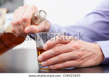 Man holding a bottle and refilling glass with whisky. - stock photo
