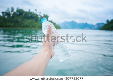 Man holding a bottle of water at lake, health care, healthy - stock photo