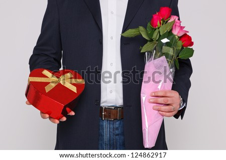 Man holding a bunch of flowers and a heart shaped box of chocolates. - stock photo