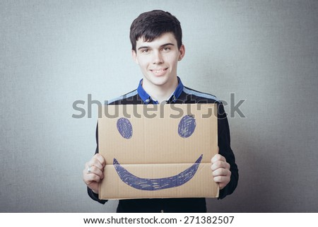 man holding a cardboard with a cheerful smiley - stock photo