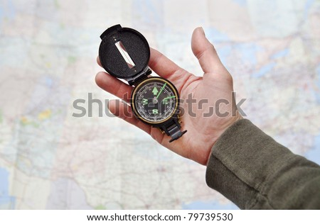 Man holding a compass over a map of the United States - stock photo