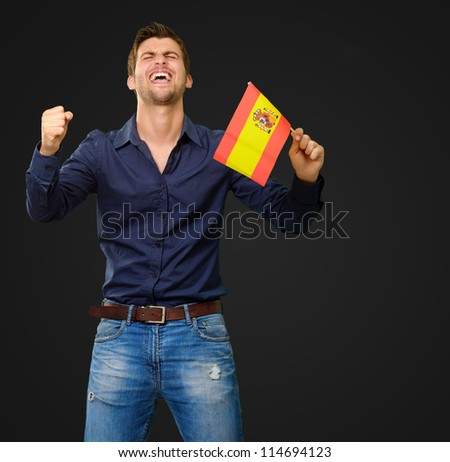 Man holding a flag and cheering on black background - stock photo